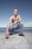 Man squatting on the sand Royalty Free Stock Images