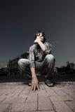 Man squatting on the street Stock Image