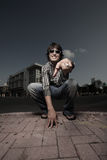 Man squatting on the street Stock Photography