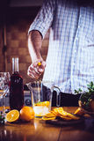 Man squeezes orange Stock Image