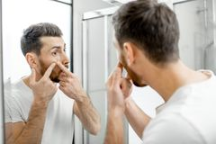 Man squeezing acne in the bathroom stock photo