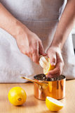 Man squeezing lemon into copper pot Stock Photos
