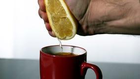 Man squeezing lemon into red mug stock video