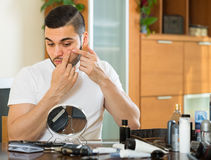 Man squeezing pimple. Adult man squeezing pimple at home royalty free stock images