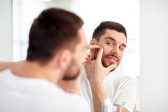 Man squeezing pimple at bathroom mirror. Beauty, hygiene, skin problem and people concept - young man looking to mirror and squeezing pimple at home bathroom stock photos