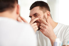 Man squeezing pimple at bathroom mirror. Beauty, hygiene, skin problem and people concept - young man looking to mirror and squeezing pimple at home bathroom royalty free stock images