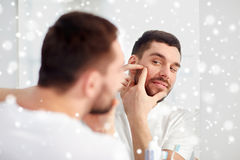 Man squeezing pimple at bathroom mirror. Beauty, hygiene, skin problem and people concept - young man looking to mirror and squeezing pimple at home bathroom stock photography