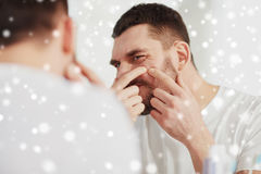 Man squeezing pimple at bathroom mirror. Beauty, skin problem, winter, christmas and people concept - young man looking to mirror and squeezing pimple at home stock photos
