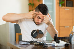 Man squeezing pimple. Guy squeezing pimple at home stock photos
