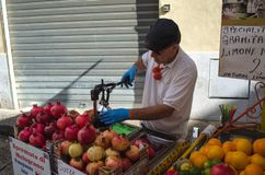 A man is squeezing pomegranate in the Historic Capo market in Palermo, Sicily stock images