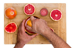 Man squeezing ruby grapefruit halves Royalty Free Stock Photography