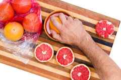 Man squeezing store bought fresh ruby grapefruits Royalty Free Stock Images