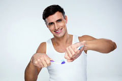 Man squeezing toothpaste on toothbrush. Happy man squeezing toothpaste on toothbrush over gray background Stock Images