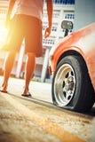 Man ställningen nära det plana gummihjulet för bilhjulet i parkeringen Arkivfoto