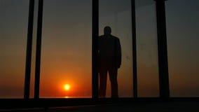 Man stående glass dörrar av huset på solnedgången lager videofilmer
