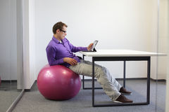 man on stability ball at desk Royalty Free Stock Photography