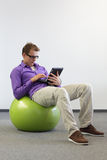 Man on stability ball working with tablet. Young man on stability ball working with tablet - relaxed position at work Stock Image