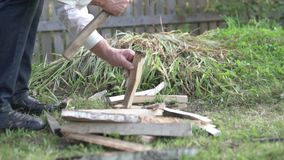 A man stabs firewood in the garden with an ax.  stock video footage