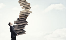 Man with stack of books in hands Royalty Free Stock Image