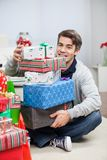 Man With Stack Of Christmas Presents At Home. Full length portrait of happy mid adult man with stack of Christmas presents sitting on floor at home royalty free stock images
