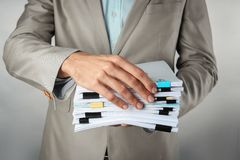 Man with stack of documents. Against light background royalty free stock image