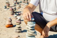 Man stacked pyramid of stones at the beach. In summer day stock photography