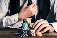 A man stacking chips on a table Royalty Free Stock Photography