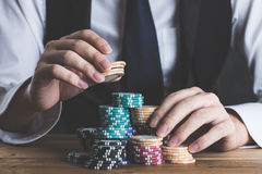 A man stacking chips on a table Royalty Free Stock Images