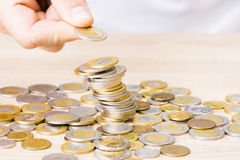 Man stacking coins. On table Stock Images