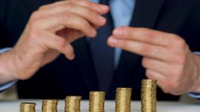 Man stacking gold coins into increasing columns stock footage