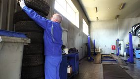 Man stacking worn tires in garage. tire changing and storing services. stock footage