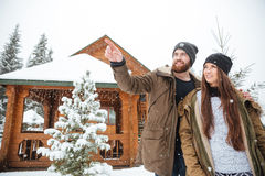 Man stading with girlfriend near log cabin and pointing away Royalty Free Stock Photo