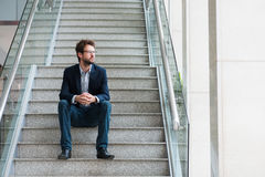 Man on the stairs. Businessman sitting on stairs and looking through window Stock Photos