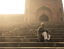 Man on Stairs Outside Jama Masjid, Old Delhi, India. Man sitting outside the mosque Stock Photo