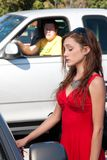 Man Stalking Woman. Young pretty woman in bright red dress unlocks her car door as a man watches stalking in the background from his pickup truck Royalty Free Stock Image