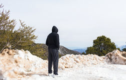 Man stand alone looking at snowy mountain landscape Stock Photo