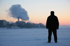 Man stand on frozen river near smoking pipes Stock Images