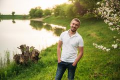 Man stand on grass. Background lake. spring time. Man stand on grass. Background lake. spring stock photo