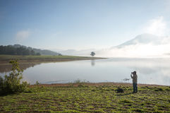 The man stand by lake anh Alone tree on the lake, sunrise at the mountai, foggy, cloud on the sky Stock Image