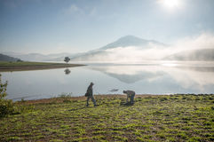 The man stand by lake anh Alone tree on the lake, sunrise at the mountai, foggy, cloud on the sky Stock Photo