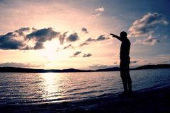 Man stand near beach looking at sunset, peaceful water level Stock Photo
