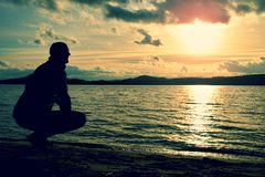 Man stand near beach looking at sunset, peaceful water level Royalty Free Stock Photo