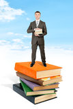 Man stand on pile of book and hold books Stock Photography