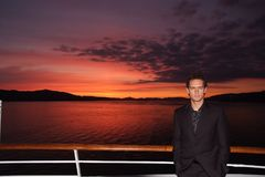 Man stand on ship deck on dramatic sky over sea in Bergen, Norway. Businessman enjoy sea travel in evening. Business or Royalty Free Stock Image