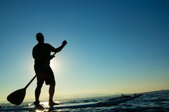 Man on Stand Up Paddle Board. With mountains in background Stock Image