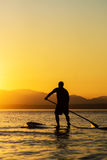 Man on Stand Up Paddle Board. With sun and mountains in background Stock Image