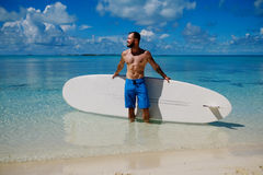 Man with Stand Up Paddle Board on the beach in Bahamas Stock Image