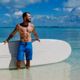 Man with Stand Up Paddle Board on the beach in Bahamas Royalty Free Stock Photo