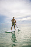Man stand up on paddle board at sunset Stock Photo