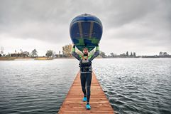 Man on stand up paddleboard. Athlete in wetsuit carries his paddleboard at wooden pier at the lake at cold weather against overcast sky stock images